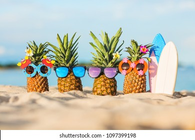 Family of funny attractive pineapples in stylish sunglasses on the sand against turquoise sea. Tropical summer vacation concept. Happy sunny day on the beach of tropical island. Family holiday. Surf