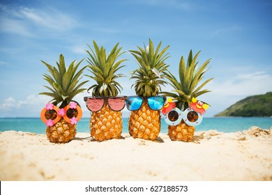 Family of funny attractive pineapples in stylish sunglasses on the sand against turquoise sea. Tropical summer vacation concept. Happy sunny day on the beach of tropical island. Family holiday - Shutterstock ID 627188573