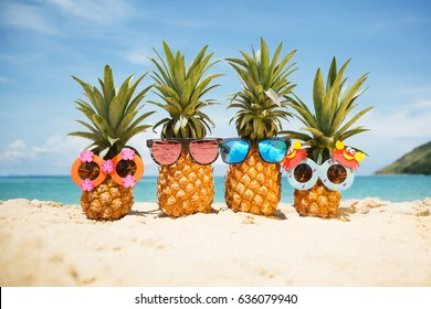 Family of funny attractive pineapples in stylish sunglasses on the sand against turquoise sea. Tropical summer vacation concept. Happy sunny day on the beach of tropical island. Family holiday