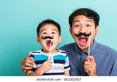 Familienlustiger glücklicher Hipster-Vater und sein Kind, das schwarze Schnurrbart hält Requisiten für den Fotostand nahe dem Gesicht, Studioaufnahme einzeln auf blauem Hintergrund, Gesundheitsbewusstsein der Männer