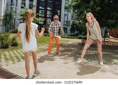 Family game. Delighted joyful family having fun while playing badminton together