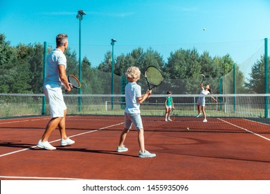 Family game. Father and son feeling involved in playing tennis against mother and daughter