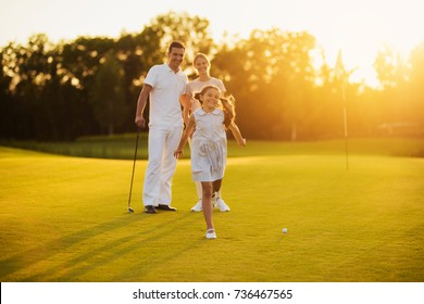 Family game of golf. A man with a woman stands next to each other with golf clubs in their hands, the girl in front of them runs toward the camera and smiles