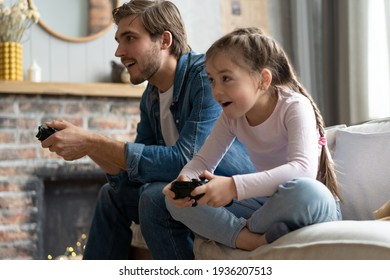 family, gaming and entertainment concept - happy father and little daughter with gamepads playing video game at home.