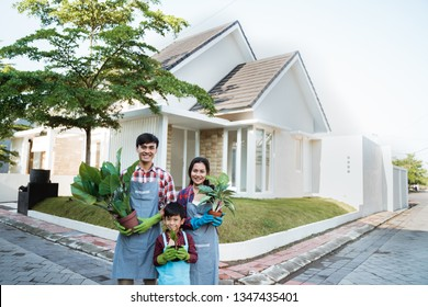 family gardening concept. asian parent with son holding a pot of plant and smiling to camera together