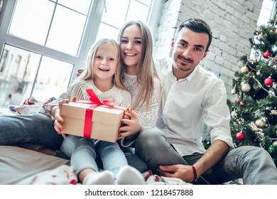 Family gather around a Christmas tree, holding a present. Happy family concept