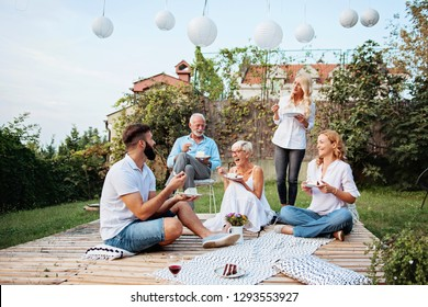 Family gathered outdoors, talking, laughing eating cake, celebrating