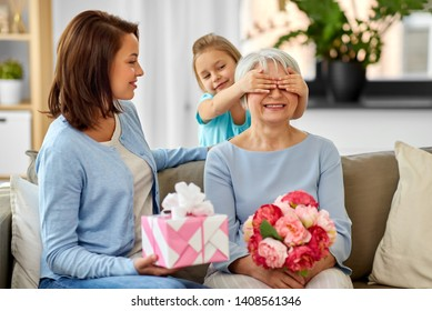 family, generation and birthday - mother and daughter greeting happy grandmother at home