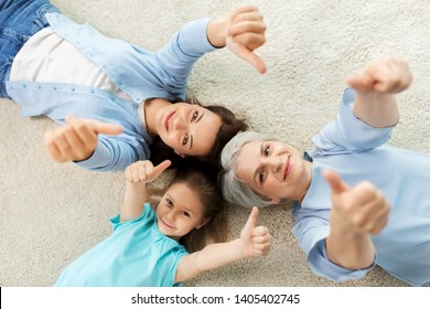 family, generation and female concept - mother, daughter and grandmother lying on floor and showing thumbs up from top