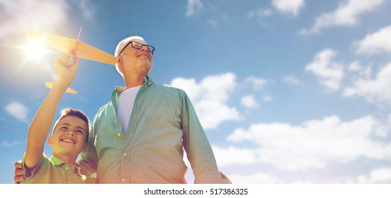 family, generation, future, dream and people concept - happy grandfather and grandson with toy airplane over blue sky and clouds background