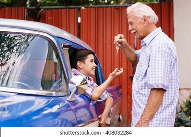 Family and Generation gap. Old grandpa spending time with his grandson. The senior man gives the keys of a vintage car from the 60s to the preteen child sitting inside. They smile happy.