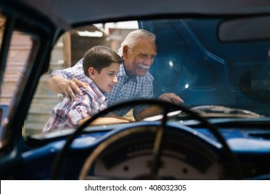 Family and Generation gap. Old grandpa spending time with his grandson. The senior man shows the engine of a vintage car from the 60s to the preteen child. They smile happy.