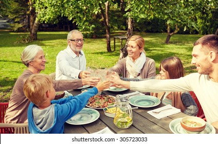 family, generation, home, holidays and people concept - happy family having dinner and clinking glasses in summer garden