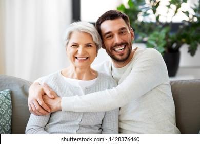 家族、世代、人々のコンセプト – 満ち足りた笑顔の老母と成人の息子が家に抱き寄せる