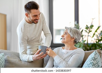 family, generation and people concept - happy smiling adult son bringing coffee to senior mother at home
