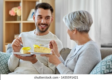 family, generation and people concept - happy smiling senior mother and adult son eating cake at home