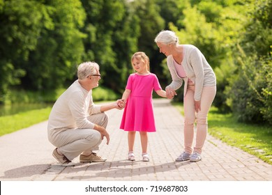 family, generation and people concept - happy smiling grandmother, grandfather and little granddaughter at park