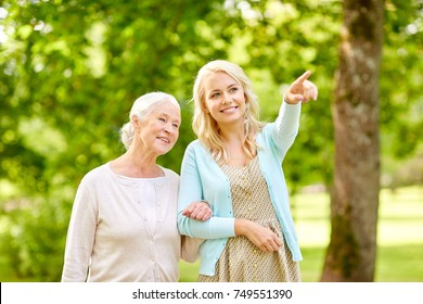 family, generation and people concept - happy smiling young daughter with senior mother at park