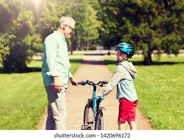 family, generation, safety and people concept - happy grandfather and boy with bicycle and bike helmet talking at summer park