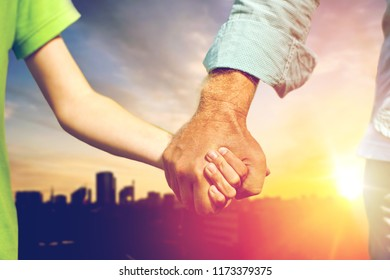 family, generation and support concept - close up of grandfather and grandson holding hands