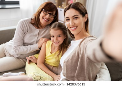 family, generation and technology concept - happy mother, daughter and grandmother taking selfie by smartphone at home