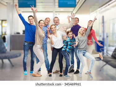 family, generation, travel, tourism and people concept - group of happy men, women and boy having fun and waving hands over airport waiting room background