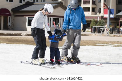 Family Gets Ready to Ski with Toddler Boy at a Winter Resort in the United States. All Dressed Safely with Helmets. Safety Bar is Down on Lift.