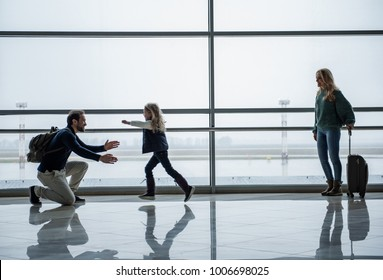 Family getting back together after time apart. Glad child running towards daddy. Mom is looking at them with joy