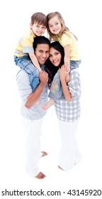 Family giving children piggyback ride against white