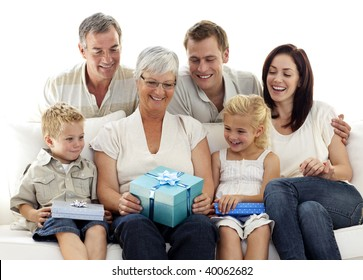 Family giving a gift to grandmother for her birthday