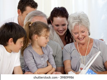Family giving a present to the grandmother at home
