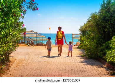 Family go to sea beach. Mother and her children on summer vacation. Tropical rest in Spain