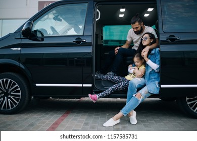 The family goes on a trip in the minivan. Happy family sitting in van car