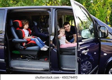 the family goes on a trip in the minivan. Father with son and daughter sitting in the salon van and smiling. Family trip