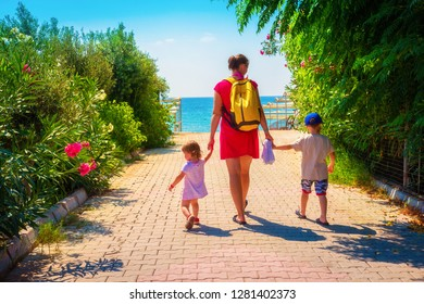 Family going to sea beach on summer vacation. Mother and children go to sea beach