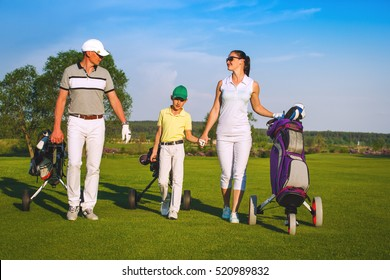 Family golfers walking on golf course at sunny day