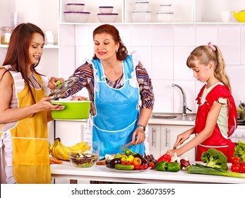 Family with grandmother and child cooking at kitchen.
