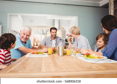 Family with grandparents discussing at dining table in home