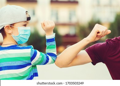 Family greeting style with elbows. Coronavirus quarantine. Social distancing concept. Family, lifestyle, new style of greetings. Kid and father greeting with elbows outdoors. Coronavirus prevention.