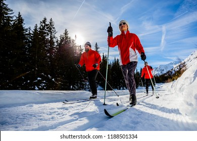 A family group of cross country skiers on a sunny winter morning in Swiss Alps, Thyon, Valais.