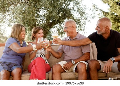 family group relaxes amused in the garden toasting with an aperitif sitting on a sofa outdoors