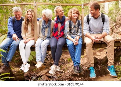 Family group sitting on a bridge in a forest, full length