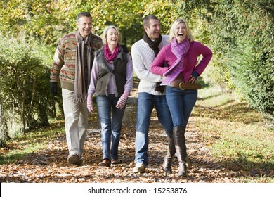 Family group walking through autumn woods