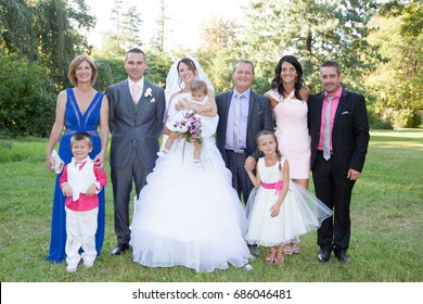 Family Group At Wedding Multi generation couple with parents and little kids. Just married. Family photo memory. Wedding dresses.