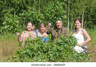 Family in a grove do birch besoms for a bath-house