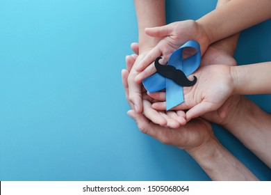 Family hands holding light blue ribbonwith mustache on blue background , Prostate Cancer Awareness, Men health awareness, Movember November Blue