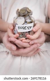 "Family Hands holding a money jar of Australian money with ""Invest"" label"
