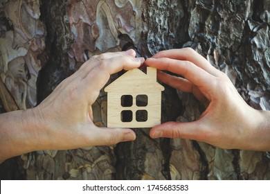 mains de famille tenant une petite maison en bois contre l'écorce d'arbre, l'immobilier et le concept de placement familial