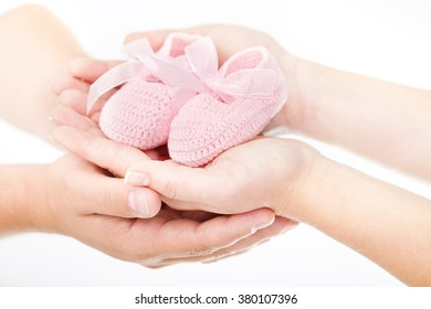 Family Hands, Mother and Father Hand Holding Pink Newborn Baby Booties, New Born Girl