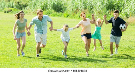 positive family happily playing and running together outdoors on green meadow